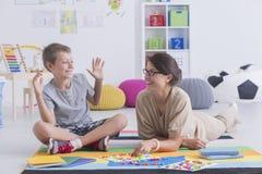 Baby-sitter que joga com menino Imagem de Stock