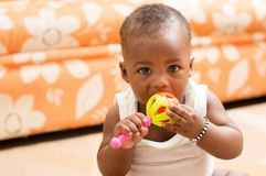 Child eating toy. Baby sitting alone in the living room eating his toy and looking at the camera Stock Image