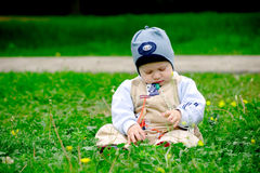 Baby sitting amoung flowers. Baby boy sitting in green grass in spring royalty free stock photos