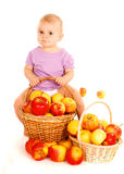 Baby sitting on apples basket Stock Images