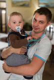 Baby sitting on the arms of his father. Royalty Free Stock Photo