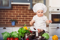 Baby sitting astride a stainless pan royalty free stock images