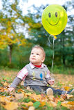Baby sitting in autumn leaves holding a balloon Stock Image