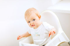 Baby sitting in baby chair and making funny face Stock Photos