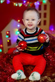 Baby sitting on background of a garland of lights and holding a red Christmas balls Royalty Free Stock Photos