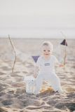 Baby sitting at the beach Stock Image