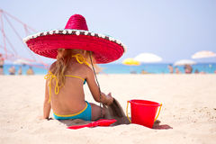 Baby sitting on the beach in a red hat. And playing in the sand Royalty Free Stock Images