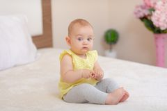 Baby sitting on the bed. stock photo