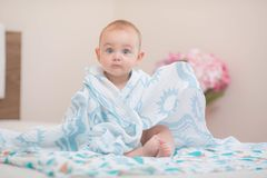 Baby sitting on the bed. royalty free stock image
