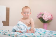 Baby is sitting in bed and looking. stock photography