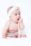 Baby sitting on a bed with a pearl necklace Stock Images