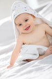 Baby sitting on a bed after taking a bath Stock Photography