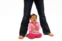 Baby sitting beneath mommy's legs Stock Photo