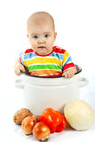 Baby sitting in the big saucepan with vegetables. Royalty Free Stock Images