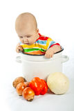 Baby sitting in the big saucepan with vegetables. Royalty Free Stock Photos