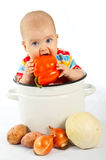 Baby sitting in the big saucepan with vegetables. Royalty Free Stock Image