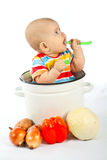 Baby sitting in the big saucepan with vegetables. Stock Photo