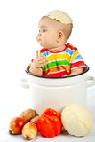 Baby sitting in the big saucepan with vegetables. Stock Image