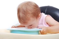 Baby sitting on the black chair eating. Baby sitting on the black chair and eating isolated in white Royalty Free Stock Photography