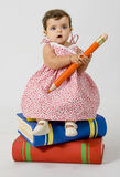 Baby sitting on books. A baby is sitting on some books stock photos