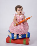 Baby sitting on books. A baby is sitting on some books stock photography