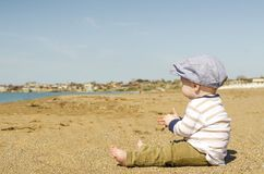 Baby Sitting in Brown Sand Stock Image
