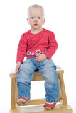 Baby sitting on a chair. Surprised little girl sitting on a chair Royalty Free Stock Photography