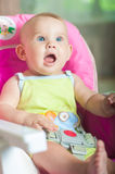 Baby sitting in a chair for feeding. At home Royalty Free Stock Photo