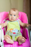 Baby sitting in a chair for feeding. At home Royalty Free Stock Image