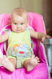 Baby sitting in a chair for feeding Royalty Free Stock Images