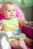 Baby sitting in a chair for feeding. At home Royalty Free Stock Images