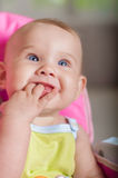 Baby sitting in a chair for feeding. And smiling Royalty Free Stock Photo