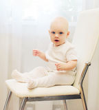 Baby sitting on chair at home and looks on camera royalty free stock photo