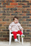 Baby sitting on a chair looking up Stock Image