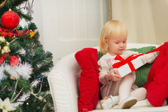 Baby sitting on chair and open Christmas present Stock Images