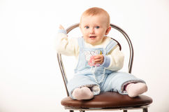 Baby sitting on a chair, studio Stock Image