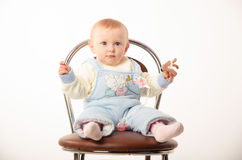 Baby sitting on a chair, studio. A child sits on a chair, the girl dressed in overalls Royalty Free Stock Image