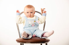 Baby sitting on a chair, studio. A child sits on a chair, the girl dressed in overalls Royalty Free Stock Photo