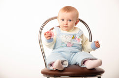Baby sitting on a chair, studio. A child sits on a chair, the girl dressed in overalls Royalty Free Stock Images