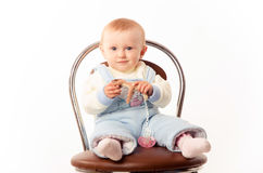 Baby sitting on a chair, studio. A child sits on a chair, the girl dressed in overalls Royalty Free Stock Photos