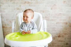 Baby sitting in chair in sunny kitchen. Healthy nutrition for kids. copy space royalty free stock image