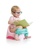 Baby sitting on chamberpot with book. Baby girl sitting on chamberpot with book royalty free stock photography