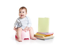 Baby sitting on chamberpot with books Stock Photos