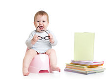 Baby sitting on chamberpot with books Royalty Free Stock Photography