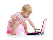 Baby sitting on chamberpot with notebook. Baby girl sitting on chamberpot with notebook stock photography