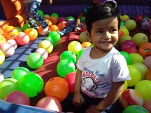 Baby sitting among colorful balls all around Stock Photography