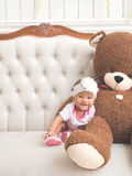 Baby sitting on a couch with big brown bear doll Stock Images