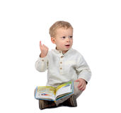 Baby sitting cross-legged reading a book Stock Images