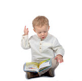 Baby sitting cross-legged reading a book Royalty Free Stock Images