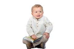 Baby sitting cross-legged reading a book Stock Image